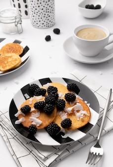 Naleśniki z jeżynami i wiórkami kokosowymi na białym stole. domowe śniadanie bezglutenowe