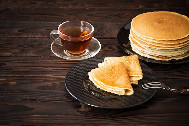 Naleśniki z miodem i filiżanką herbaty na starym drewnianym tle