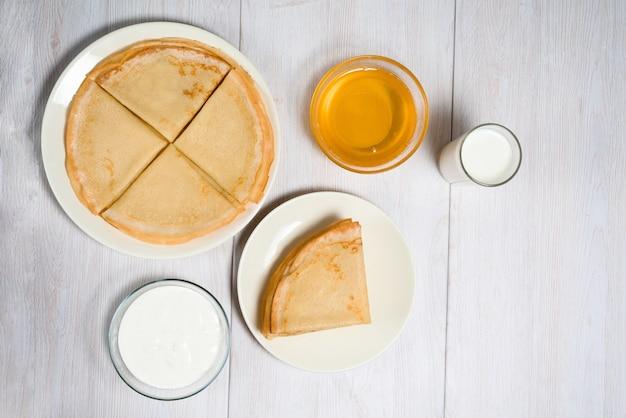 Naleśniki z miodem, śmietaną i mlekiem na lekkim drewnianym stole