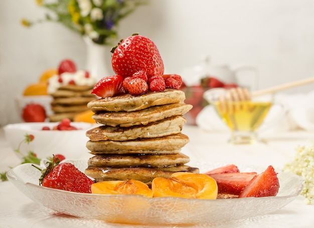 Naleśniki z miodem, truskawkami i owocami z bliska