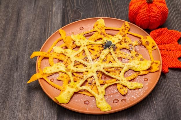 Naleśniki z pajęczej sieci z syropem cukrowym i proszkiem na śniadanie halloween. z szydełkową pomarańczową dynią i liściem