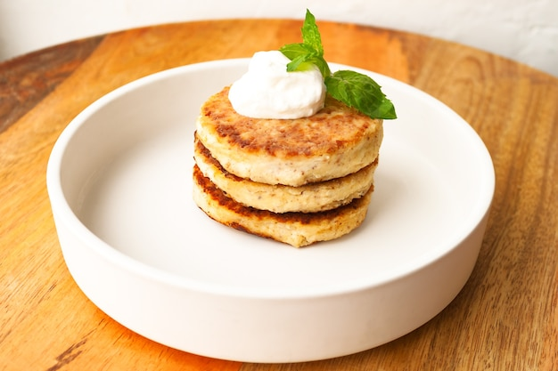 Naleśniki z twarogiem lub placki twarogowe z miętą kwaśną śmietaną ozdobione migdałami i mąką kokosową bezglutenowe na białym talerzu widok z bliska. zdrowe jedzenie śniadanie. selektywna nieostrość.