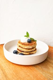 Naleśniki z twarogiem lub placki twarogowe ze śmietaną, liściem mięty i jagodami z migdałów i mąki kokosowej bez glutenu w białej płytce z bliska widok. koncepcja śniadanie. selektywna nieostrość.