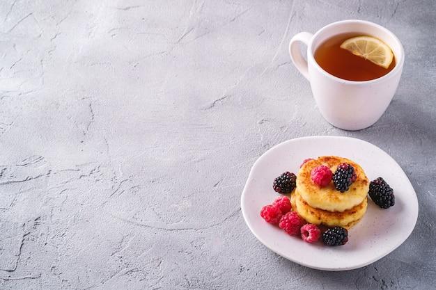Naleśniki z twarogu, deser twarogowy z malinami i jagodami jeżyny na talerzu w pobliżu filiżanki gorącej herbaty z plasterkiem cytryny na kamiennym betonowym tle, widok pod kątem