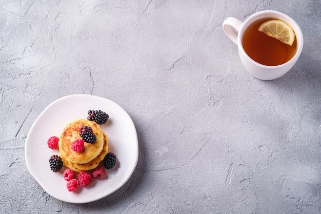 Naleśniki z twarogu, deser twarogowy z malinami i jagodami jeżyny na talerzu w pobliżu filiżanki gorącej herbaty z plasterkiem cytryny