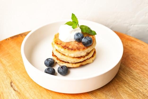 Naleśniki z twarogu lub placki twarogowe ze śmietaną, liściem mięty i jagodami z migdałów i mąki kokosowej bez glutenu na białym talerzu z bliska. zdrowe jedzenie śniadanie. selektywna ostrość.