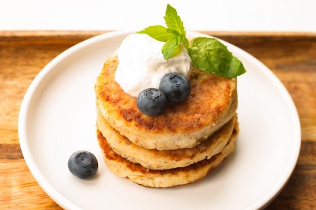 Naleśniki z twarogu lub placki twarogowe ze śmietaną, liściem mięty i jagodami z migdałów i mąki kokosowej bez glutenu w białej płytce na drewnianej tacy z bliska widok z góry. koncepcja śniadanie