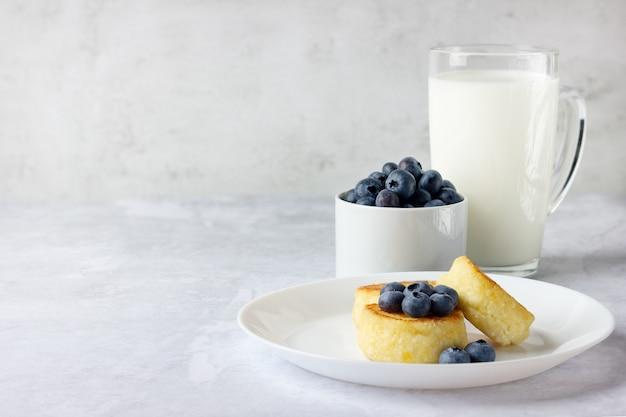 Naleśniki z twarogu ze świeżymi jagodami i mlekiem. domowe jedzenie. skopiuj miejsce na twój tekst. zdrowe śniadanie.