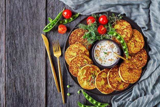 Naleśniki z zielonego groszku i płatków owsianych na białym talerzu z prostym greckim sosem jogurtowym ze świeżymi kiełkami grochu i pszenicy, koncepcja zdrowej diety, widok poziomy z góry, układanie na płasko, wolna przestrzeń