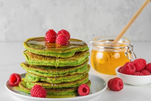 Naleśniki z zielonej herbaty matcha. kupie domowe naleśniki ze świeżymi malinami i miodem. zdrowy deser śniadaniowy