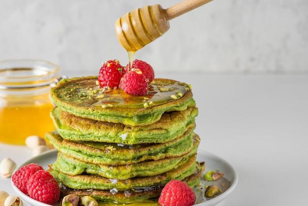 Naleśniki z zielonej herbaty matcha. kupie domowe naleśniki ze świeżymi malinami, pistacjami i płynącym miodem