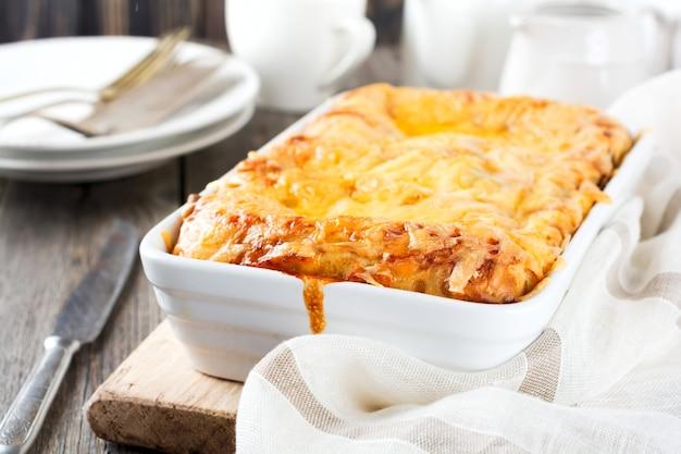 Naleśniki zapiekane z kurczakiem, pieczarkami, szpinakiem i serem w białej ceramicznej formie.