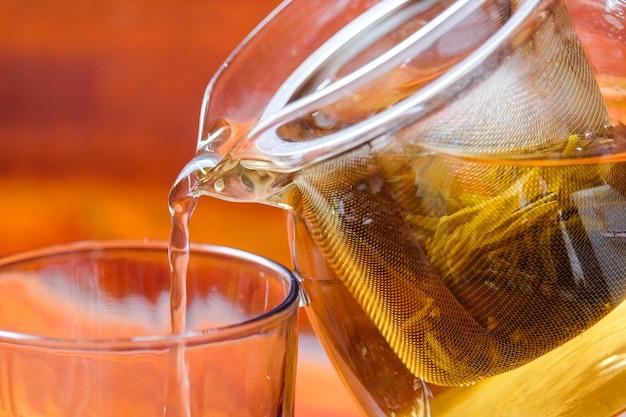 Nalewać gorącą chińską herbatę herbacianym producentem z zieloną herbatą opuszcza dla backgroud lub tekstury - kucbarski (napój) pojęcie.