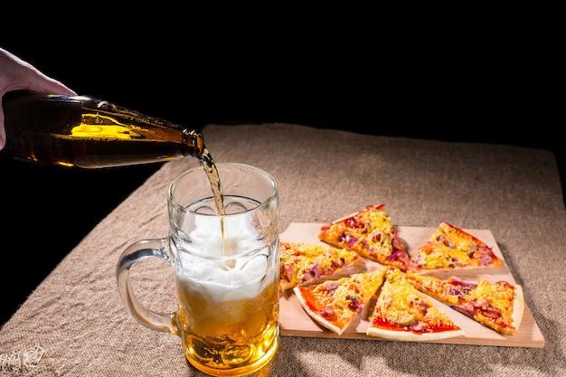 Nalewanie butelkowego piwa do szklanego kubka z posiłkiem świeżo upieczonej pizzy ułożonej w plasterki na drewnianej desce do krojenia na stole pokrytym jutą