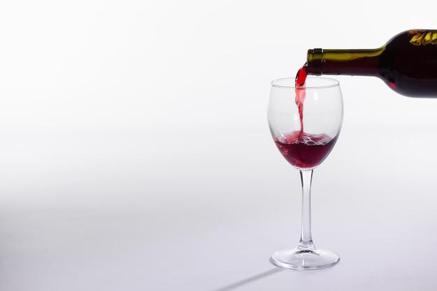 Nalewanie czerwonego wina do kieliszka na białym tle z miejscem na kopię