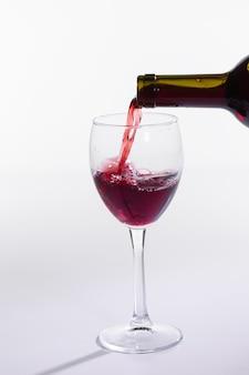 Nalewanie czerwonego wina do kieliszka na białym tle