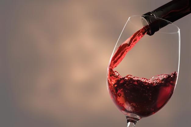 Nalewanie czerwonego wina do szklanki z butelki na rozmytym beżowym tle, zbliżenie. miejsce na tekst