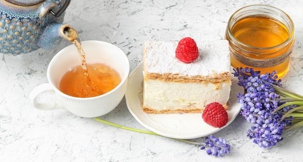 Nalewanie herbaty do filiżanki z jasnoniebieskiego ceramicznego czajniczka z kremowym ciastem ozdobionym malinami