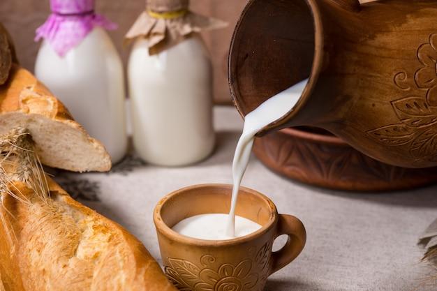 Nalewanie kubka świeżego mleka na śniadanie do rustykalnego kubka ze świeżo upieczonym chlebem