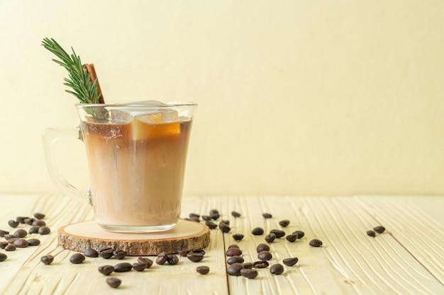 Nalewanie mleka do czarnej szklanki do kawy z kostką lodu, cynamonem i rozmarynem na drewnianym stole