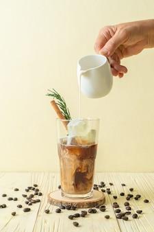 Nalewanie mleka do czarnej szklanki do kawy z kostkami lodu, cynamonem i rozmarynem na powierzchnię drewna