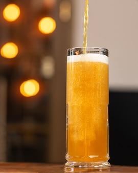 Nalewanie piwa, nalewanie do kufla, szklanka z tłem bokeh