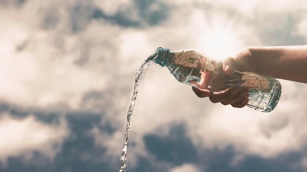 Nalewanie przezroczystej plastikowej butelki z czystą wodą pitną odświeżającą i rozchlapaną.