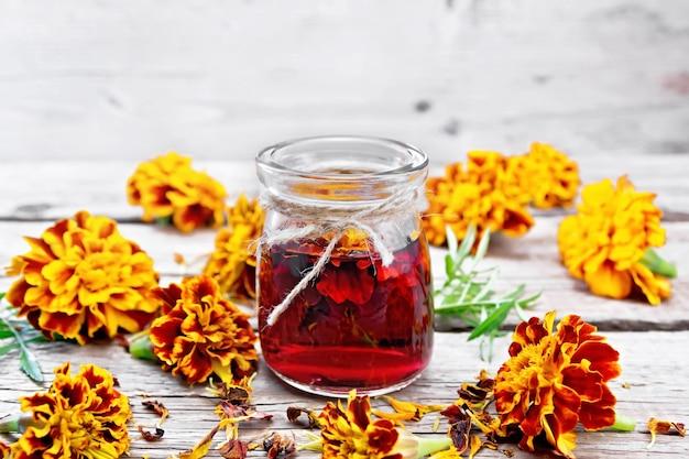 Nalewka alkoholowa z nagietków w szklanym słoju, świeże i suszone kwiaty z zielonymi liśćmi na tle deska