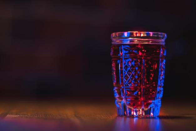 Nalewka koloru czerwonego w kryształowym szkle stoi na drewnianym stole w niebieskim oświetleniu