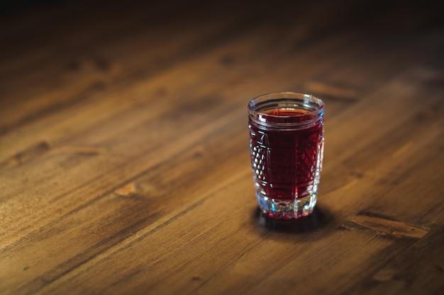 Nalewka koloru czerwonego w kryształowym szkle stoi na drewnianym stole