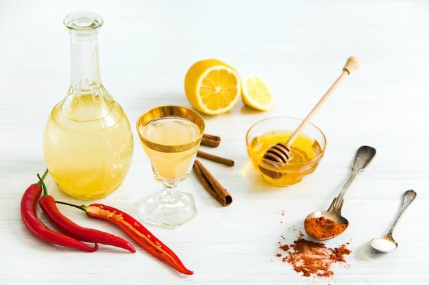 Nalewka z czerwonej papryki domowej w szklance i świeżych cytryn na drewnianym stole