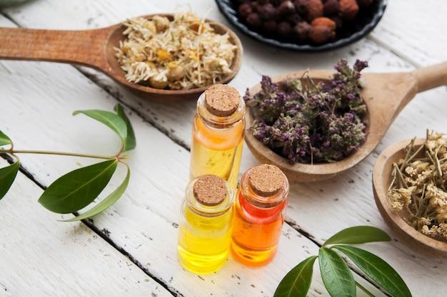 Nalewki zioła w szklanych butelkach i suche zioła na drewnianym stole. koncepcja tradycyjnej medycyny i leczenia ziołami.