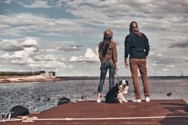 Należą do siebie. widok z tyłu na całej długości pięknej młodej pary odwracającej wzrok, stojąc z psem na brzegu rzeki
