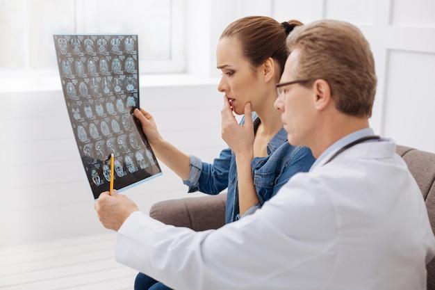 Należy to natychmiast leczyć. zaniepokojony profesjonalny neurochirurg pokazujący pacjentce skan mózgu i wskazujący na niektóre problemy, podczas gdy ona uważnie słuchała