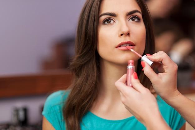 Nałożenie błyszczyka na usta pięknej kobiety
