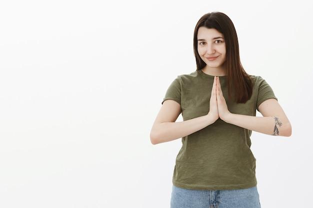 Namaste niech pokój będzie z tobą. portret uroczej i zrelaksowanej, dobrze wyglądającej młodej kobiety w wieku 20 lat z tatuażem i brązowymi włosami trzymającej dłonie razem w pozie modlitwy lub buddy, uśmiechającej się nad szarą ścianą