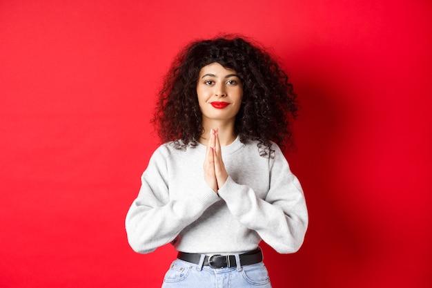 Namaste. wdzięczna młoda kobieta z kręconymi włosami i czerwonymi ustami okazuje wdzięczność, uśmiecha się zadowolony, stojąc na ścianie studia.
