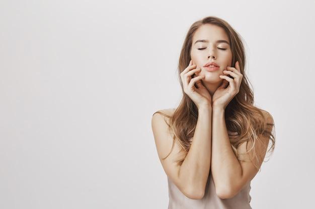 Namiętna kobieta zamyka oczy i delikatnie dotyka skóry
