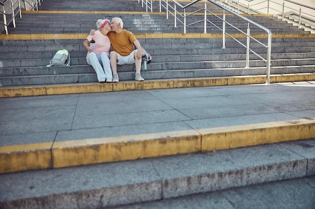 Namiętna siwowłosa kobieta z butelką sportową w dłoni całuje zadowolonego starszego męża