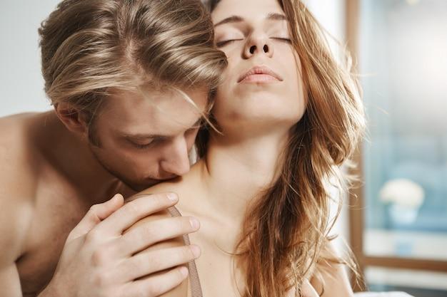 Namiętne zdjęcie sypialni przystojnego faceta o jasnych włosach w łóżku z atrakcyjną kobietą, przytulającego ją od tyłu i całującego na ramieniu, a oczy miała zamknięte. czuła para w środku erotycznego momentu