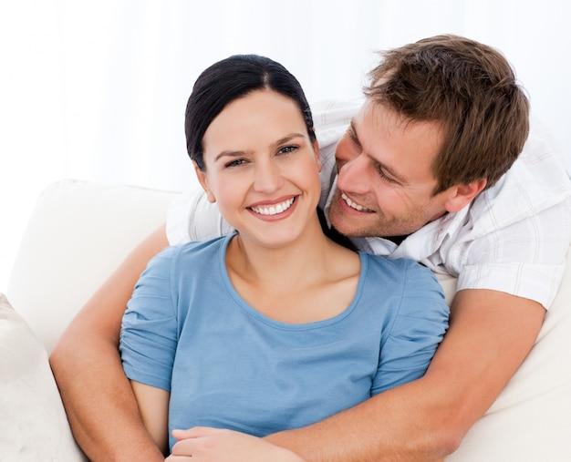 Namiętny mężczyzna ściska jego dziewczyny podczas gdy relaksujący na kanapie
