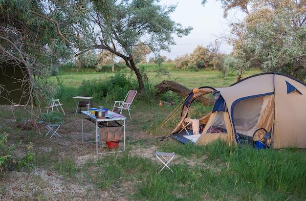Namiot kempingowy na plaży. przygoda turystyka kempingowa i namioty i samochody nad morzem lub jeziorem.