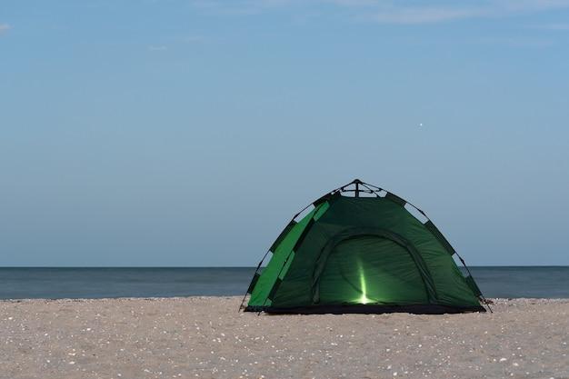Namiot kempingowy nad brzegiem morza świecący od wewnątrz. wieczór
