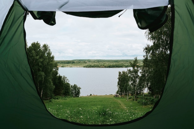 Namiot kempingowy nad brzegiem rzeki w malowniczym krajobrazie