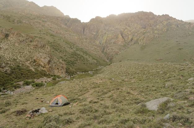 Namiot kempingowy wśród hipnotyzujących gór pod zachmurzonym niebem