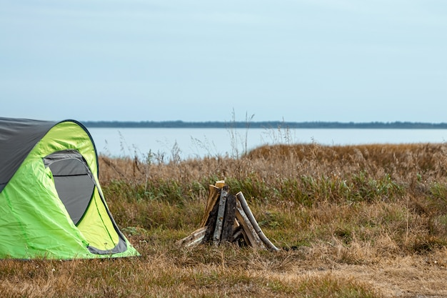 Namiot kempingowy zielony w tle przyrody i jeziora. podróże, turystyka, camping.