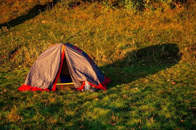 Namiot nad brzegiem jeziora przy pięknym zachodzie słońca (świt)
