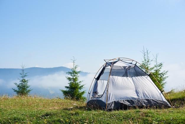 Namiot turystyczny na trawiastym wzgórzu