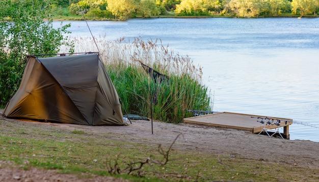 Namiot w pobliżu brzegu jeziora o zachodzie słońca i wędka karpiowa w słodkiej wodzie