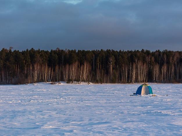 Namiot wędkarski na zamarzniętym zaśnieżonym jeziorze